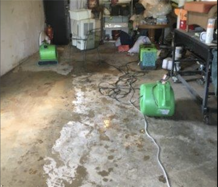 Garage area with pool of water on the cement floor and green drying equipment set up.
