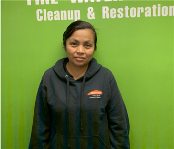 Female employee in front of green wall.