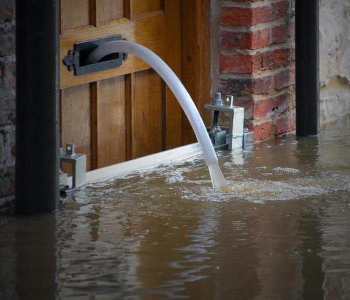Flood water pouring out of a brown door